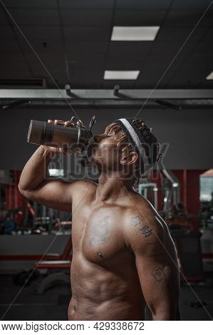 Nutritional Supplement. Muscular Athletic Man Drinking Protein, Energy Drink After Workout In Gym
