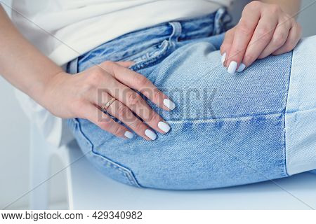 Womans Hands With Perfect Manicure Wears In Denim Trousers And White Basic T-shirt.
