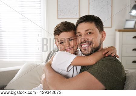 Father And His Son On Sofa In Living Room. Adoption Concept