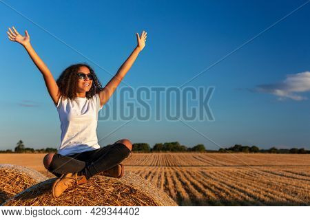 Beautiful, happy mixed race African American female girl child teenager young woman celebrating arms raised in sunshine wearing sunglasses and smiling with perfect teeth