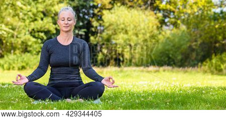 Panoramic web banner header of mature middle aged fit healthy woman practicing yoga outsidein a natural tranquil green environment panorama.
