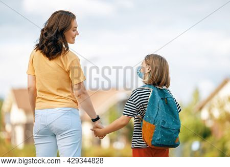 Parent and pupil of secondary school going hand in hand. Woman and girl with backpack behind the back. Beginning of lessons.