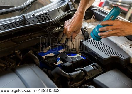 Mechanic Holding And Shining Flashlight To Checking A Car Engine Problem. Car Mechanic Technician Ho