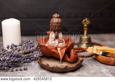 Calming Zen Interiors With Buddha Statue. Buddha Statue In The Smoke Of Incense On Black. Candle Inc