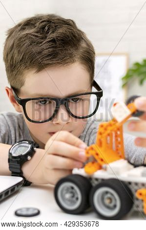 Close-up Of A Clever Boy In Eyeglasses Builds And Programs A Robot Car At Home. The Child Is Learnin