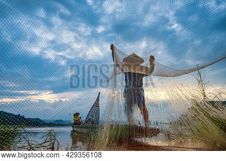 In The Early Morning Before Sunrise, An Asian Fisherman On A Wooden Boat Casts A Net For Catching Fr