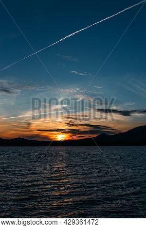 Beautiful Mountain Lake At Sunset, Vertical View. A Lake Among The Mountains At Sunset. Evening Land