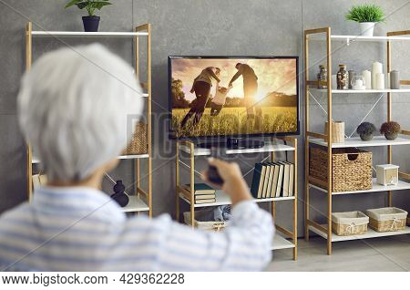 Senior Woman Watching A Movie Or A Tv Show On A Large Modern Television Set At Home