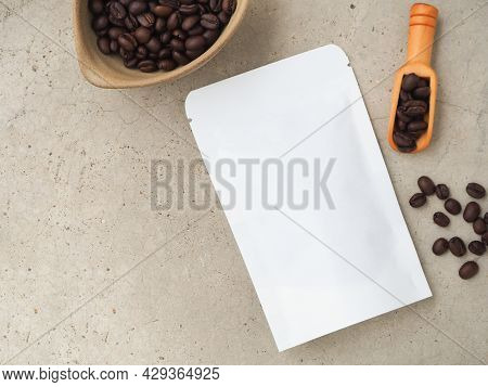 White Paper Bag With Zipper And Coffee Beans In A Bowl, Wooden Scoop On A Grey Background. Top View
