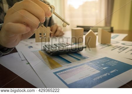 The Concept For Real Estate. Real Estate Agent Holding House Key On Table With Calculator, House Des