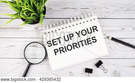 Set Up Your Priorities Text Concept Write On Notebook With Office Tools On Wooden Background
