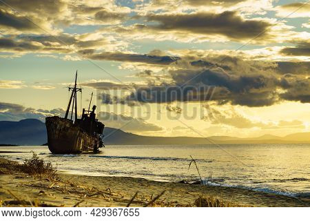 An Old Abandoned Shipwreck, Wrecked Boat Sunken Ship Stand On Beach Coast. Scenic Sunset Sky