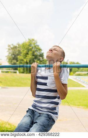 Outdoor Portrait Of Blond Boy Teenager, Young Man On Brachiating Bar At A School Yard. Boy Doing Pul