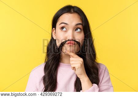 People Emotions, Lifestyle Leisure And Beauty Concept. Funny And Cute Asian Girl Making Fake Moustac