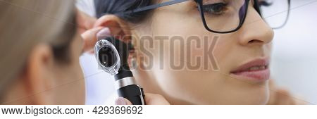 Doctor Laryngologist Examining Ear Of Female Patient With Glasses Using Otoscope