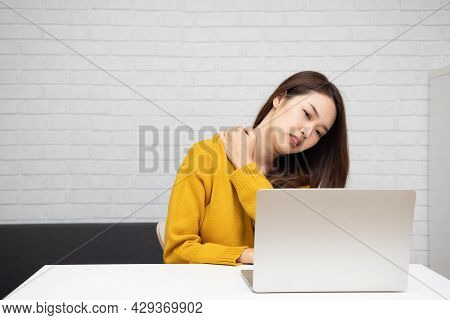 Young Asian Woman Suffering From Neck Pain While Using Laptop Computer, Office Syndrome And Work Fro