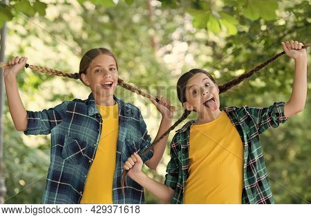 Funny Children Hold Long Hair Plaits Grimacing Mouths In Casual Fashion Style Summer Outdoors, Salon