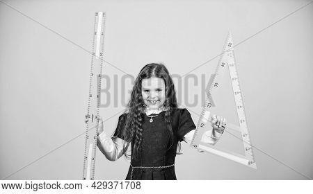 Sizing And Measuring. Pupil Cute Girl With Big Ruler. School Student Study Geometry. Kid School Unif