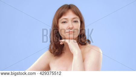 Confident Middle Aged Woman Looks At Camera With His Hand Near The Chin. Nude Beautiful Caucasian Wo