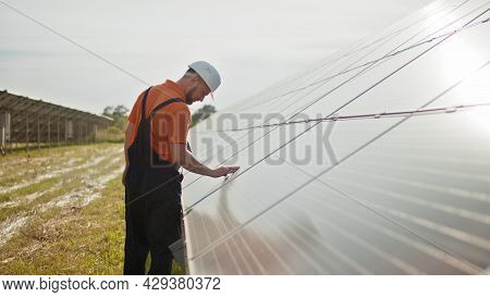 Professional Male Engineer In Protective Helmet Walk On Ecological Solar Plant Construction. Concept