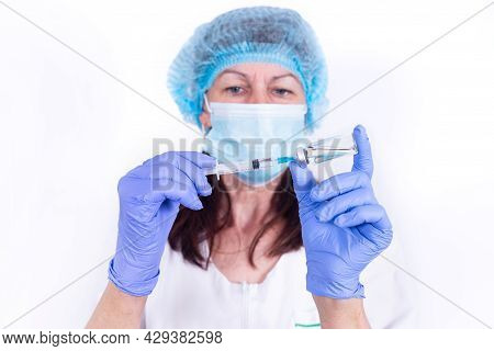 Female Doctor In Protective Mask And Gloves Is Typing Vaccine Into Syringe. Close-up. Virologist Sci