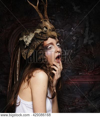 Young woman with bright makeup, braids and a skull on her head, posing over dark background party, carnival, halloween.