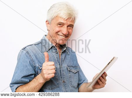 lifestyle, tehnology and people concept: Happy senior man using digital tablet and show thumbs up over white background.