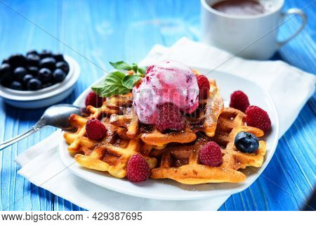 Belgian waffles with fresh berries and ice cream over wooden background. Close up.