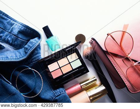 Top view of woman jeans shirt, concealer pallet, lip gloss, nail polish, bracelet, powder brush on white background. beauty and fashion concept.