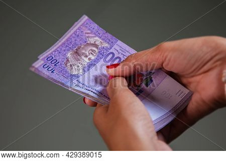 Female Hands With Red Nails Counting 100 Ringgit Banknote. Ringgit The Currency Of Malaysia. Woman H