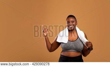 Chubby Black Woman In Sportswear Pointing At Free Space