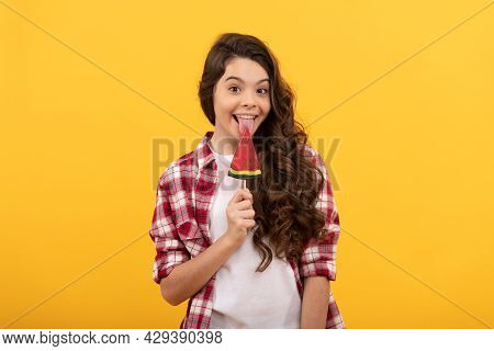 Happy Kid With Long Curly Hair Lick Lollipop Caramel Candy On Yellow Background, Childhood.
