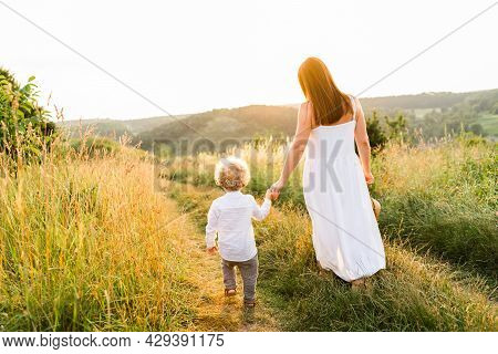 Mother And Son Are Walking Holding Hand In A Beautiful Hilly Area At Sunset