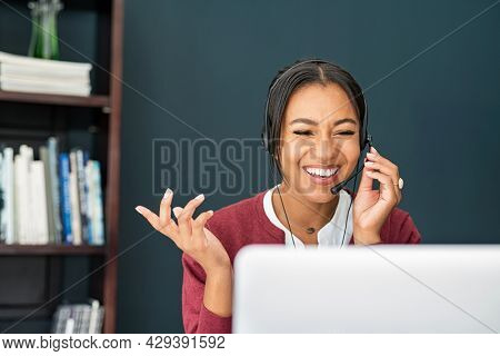 Smiling african mature woman doing video call using laptop. Mid adult indian businesswoman with headset talking during online meeting with colleague. Indian happy woman working from home.