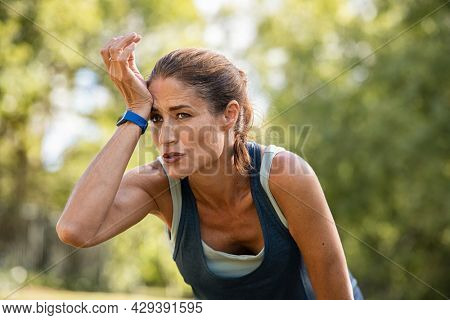 Exhausted mature woman after jogging. Sweaty middle aged athlete taking a break from running at park with copy space. Tired mid adult woman wipes wet forehead after intense fitness training.