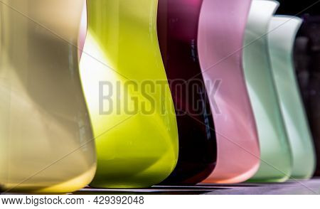 Vases For Flowers Are Glass Colored Standing In A Row With A Perspective. Abstract Glass Vases Color