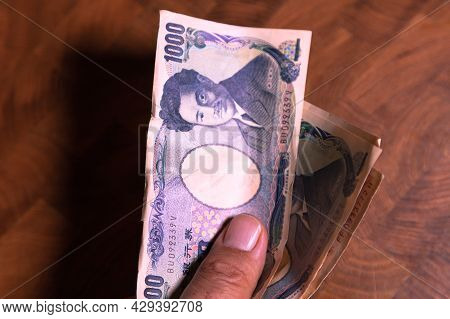 Male Hands Shows Japanese Yen. Yen Is The Currency Of Japan. On The Obverse Side Of The Banknote Hid