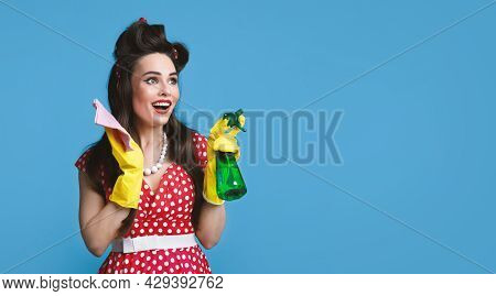 Emotional Pinup Lady In Retro Style Clothes Posing With Rag And Spray Detergent On Blue Studio Backg