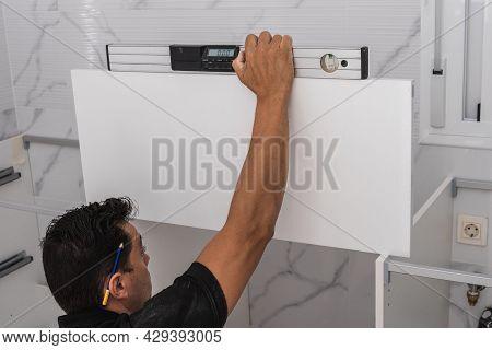 Man Using A Spirit Level To Install A Kitchen Unit