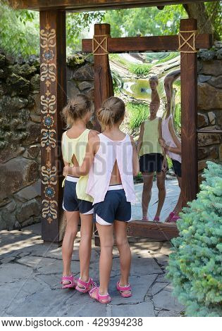 Twins Caucasian Girls In Front Of Distorting Mirror