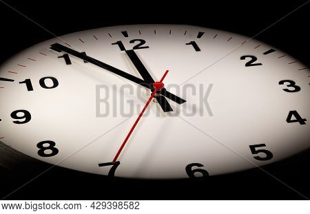It's Five To Twelve, The Clock Is Ticking. Modern Wall Clock Shows The Time 5 Before 12. Close Up To