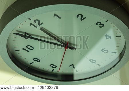 It\'s Five To Twelve, The Clock Is Ticking. Modern White Clock Shows The Time 5 Before 12. Close Up