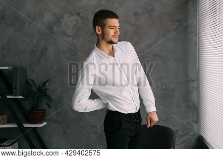 Office Worker With Back Pain Standing Against The Wall Of The Office Has An Incorrect Posture, Pinch