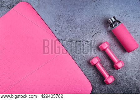 Top View Of Sport Mat, Glass Water Bottle And Pink Dumbbells On Marble Grey Background Or Set For Pi