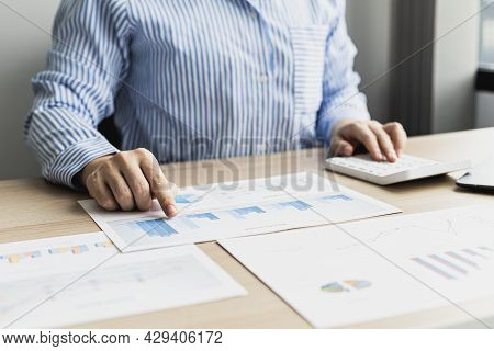 A Businesswoman Using A White Calculator To Check The Numbers On The Sales Summary From The Sales De