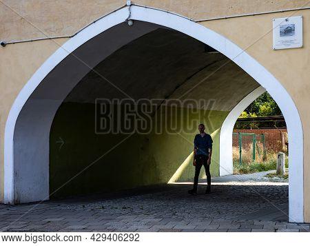 Wroclaw, Poland - July 5, 2021: A Man Walking Through The Shadowy Archway In A Historical Building.