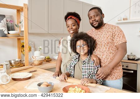 African family of two parents and cute son rolling dough while cooking pastry