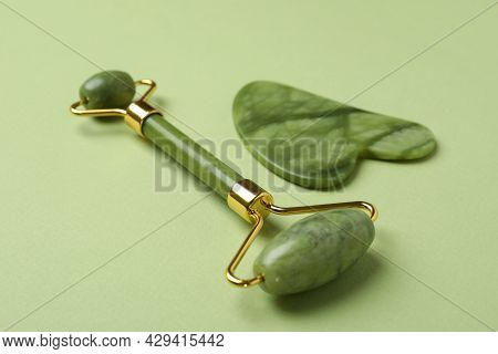 Face Roller And Gua Sha On Green Background