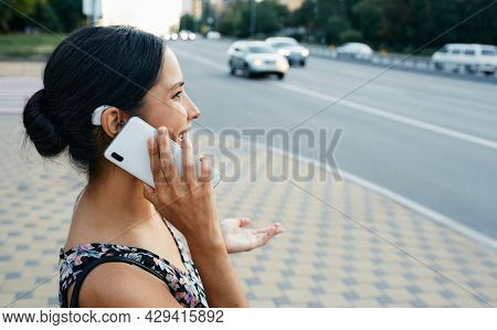 Adult Woman With A Hearing Impairment Uses A Hearing Aid In Everyday Life, Talking On Phone In Urban