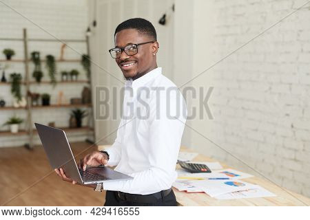 Smiling African Man Working In A Modern Office Behind A Laptop And Looking At The Camera. Handsome A